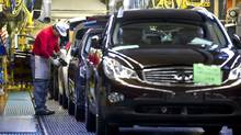 Nissan Motor Co.'s Infiniti brand vehicles bound for China, are given a final check after passing through the assembly line at the company's Tochigi plant in Tochigi Prefecture, Japan, on Thursday, Nov. 12, 2009. (Robert Gilhooly/Bloomberg)