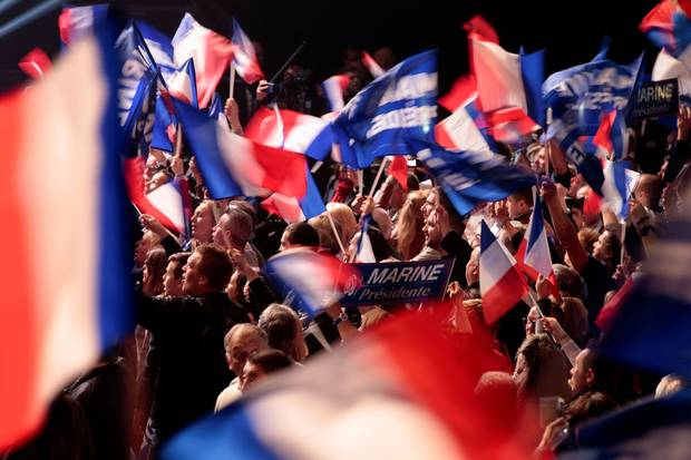 Supporters wave French national flags as they cheer ahead of a Marine Le Pen rally in Paris on April 17, 2017.