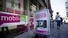 A person uses a mobile phone while walking by a Mobilicity store in Toronto. (Michelle Siu For The Globe and Mail)