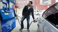 Mostafa Mahmood puts gas in his car in Montreal in April. High prices don't seem to have fazed Americans and Canadians planning their summer holidays. (Graham Hughes for The Globe and Mail/Graham Hughes for The Globe and Mail)