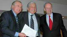 "In this undated handout, former Saskatchewan premier Roy Romanow, Chief Justice of Ontario Roy McMurtry, and former prime minister Jean Chrétien pose with the original ""kitchen accord"" compiled 25 years ago. (LAW SOCIETY OF UPPER CANADA)"