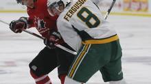 Team Canada's Tyler Graovac (L) battles University of Alberta Golden Bears' Brett Ferguson for the puck during the second period of their hockey game at the Team Canada selection camp in Calgary, Alberta, December 12, 2012. Graovac was one of five players cut from the Canadian junior hockey team on Wednesday. (TODD KOROL/REUTERS)