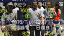 Pedestrians are reflected in the glass of a share prices board in Tokyo on August 8, 2011. (Yoshikazu Tsuno/AFP/Getty Images/Yoshikazu Tsuno/AFP/Getty Images)