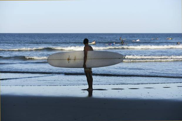 A surfer checks out the waves by Tamarindo.