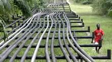 An unidentified man walks along oil pipelines in Nigeria. Despite the sale of some of its assets in Nigeria, Total SA does not plan to leave the country completely. (GEORGE OSODI/ASSOCIATED PRESS)