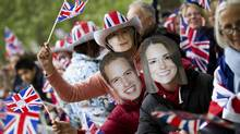 Royal supporters wave flags and wear masks depicting Britain's Prince William and Kate Middleton, along the procession route in London April 29, 2011. (Reuters/Reuters)