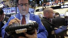 Trader Peter Costa, left, works on the floor of the New York Stock Exchange, in New York. (Richard Drew/AP)