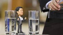 A Stephen Harper bobblehead doll rests on the podium as the Prime Minister announces the creation of the Red Tape Reduction Commission in Toronto on Jan. 13, 2011. (Darren Calabrese/THE CANADIAN PRESS)