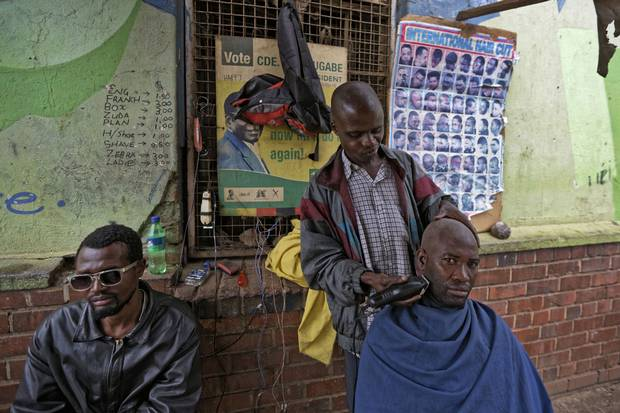 Nov. 16: A man has a shave at a street barber, next to a covered poster of Mr. Mugabe, in the low-income neighbourhood of Mbare in Harare.