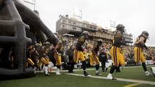 The Hamilton Tiger-Cats run onto the field to begin a game against the Winnipeg Blue Bombers at Ivor Wynne Stadium in Hamilton, ON, on Saturday, October 27, 2012. This may be the final CFL game played in the stadium.  (Matthew Sherwood/The Globe and Mail)