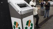 A smoker walks past a newly installed cigarette-recycling receptacle in downtown Vancouver on Nov. 12, 2013. (John Lehmann/The Globe and Mail)