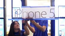 Apple employees hang an iPhone 5 sign at one of the company's retail locations shortly before sales began in San Francisco, Calif., Friday. (NOAH BERGER/REUTERS)