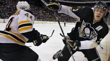 Boston Bruins' Dennis Seidenberg, left, checks Pittsburgh Penguins' Evgeni Malkin, of Russia, into the boards in the second period of an NHL hockey game in Pittsburgh,