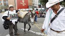 Growers protest against low worldwide prices of coffee as they lead a mule loaded with coffee beans in front of the National Federation of Coffee Growers in Bogota Nov. 28, 2012. Colombia is launching insurance to protect coffee plantations hit by climate change. (JOSE MIGUEL GOMEZ/REUTERS)