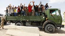 Volunteers who have joined the Iraqi Army to fight against the predominantly Sunni militants who have taken the country's north gesture from an army truck in Baghdad on June 13, 2014. (AHMED SAAD/REUTERS)