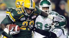 Edmonton Eskimos' Jerome Messam (L) pushes off Saskatchewan Roughriders' Tyron Brackenridge during his 1000th yard carry in their CFL football game in Edmonton November 4, 2011. REUTERS/Dan Riedlhuber (Dan Riedlhuber/Reuters)