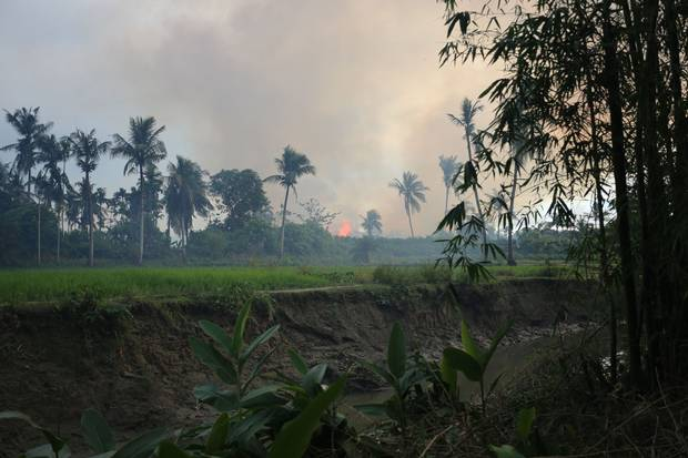 Fire consumes the home of Sakhina Begum, a Rohingya woman. Survivors of a wave of anti-Rohingya violence that began on Aug. 25 have fled the country after finding their homes destroyed.
