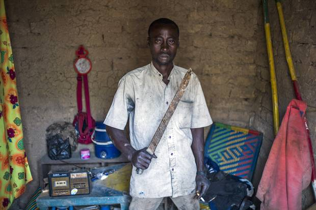 A Malian man poses at his home with a machete to protect himself from Islamist rebel groups, in Mopti, in 2013.