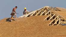 Carpenters work to enclose a roof on a home being built in Springfield, Ill., in this file photo. (Seth Perlman/The Associated Press)