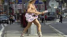 """In this Sept. 10, 2002 file photo, Robert Burck, a.k.a. """"The Naked Cowboy,"""" plays his guitar in Times Square. (ROBERT F. BUKATY/AP)"""