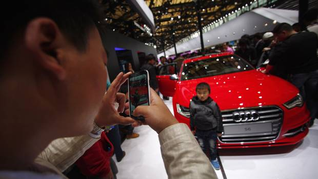 A man takes a picture of his son in front of an AUDI S6 car during the 15th Shanghai International Automobile Industry Exhibition in Shanghai April 21, 2013. (CARLOS BARRIA/Reuters)