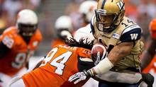 Winnipeg Blue Bombers' Aaron Woods, right, is tackled by B.C. Lions' Khreem Smith during the second half of a CFL game in Vancouver, B.C., on Monday August 5, 2013. (DARRYL DYCK/The Canadian Press)