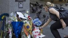 A woman places flowers at a memorial near Concordia University for Lin Jun, a Chinese student who was the victim of a murder and dismemberment, in Montreal on June 6, 2012. (CHRISTINNE MUSCHI/REUTERS)