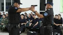 In this April 25, 2014 photo, a police training officer, right, guides a trainee during a weapons training session for police officers in Haikou, in southern China's Hainan province. (AP)