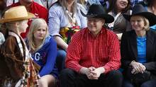 PM Stephen Harper, his wife Laureen and daughter Rachel watch the annual Stampede parade during the 100th anniversary of the Calgary Stampede in Calgary (Todd Korol/Reuters)
