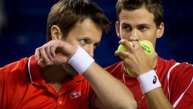 Canada's Daniel Nestor, left, of Toronto, Ont., and Vasek Pospisil, of Vernon, B.C., talk strategy while playing Italy's Daniele Bracciali and Fabio Fognini during the first set of a Davis Cup quarter-final doubles match in Vancouver, B.C., on Saturday April 6, 2013. (DARRYL DYCK/THE CANADIAN PRESS)