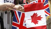 Royal watchers hold British and Canadian flags as they await the arrival of the Duke and Duchess of Cambridge at Rideau Hall in Ottawa, on June 30, 2011. (Adrian Wyld/THE CANADIAN PRESS)