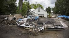 A displaced boat sits on the front lawn of a home in High River's Wallaceville neighbourhood damaged by the massive flood in High River during a media tour of the city June 25, 2013. (John Lehmann/The Globe and Mail)