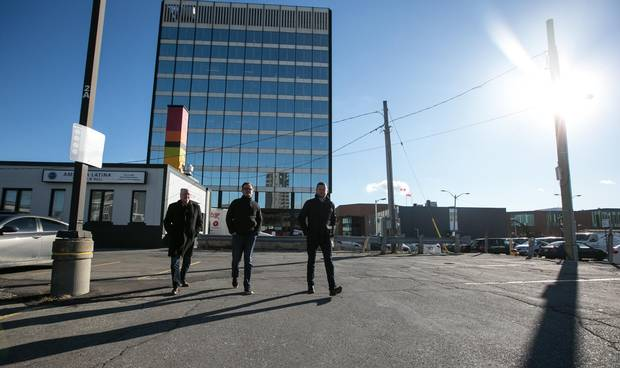 Mr. Gibson, left, Mr. Beattie and Mr. Barclay stroll through the parking lot where their new office complex is going up in downtown Kitchener The King Street West location is only a few feet from Kitchener's soon-to-open LRT line.