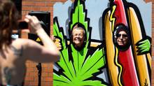 People pose for photos in cutouts near Main Street Marijuana, which began selling marijuana for recreational uses on Wednesday. Db3 Inc., meanwhile, got a licence this week to manufacture edible pot products. (Beth Nakamura/AP)
