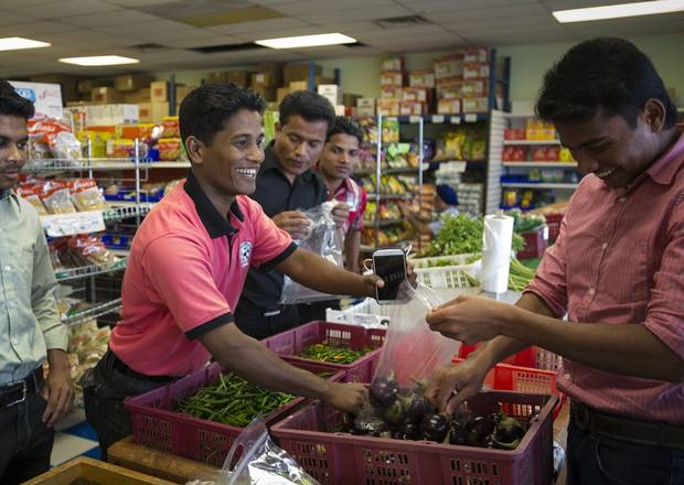 Mohammed Rafiq, third from the left in the black shirt, shops for groceries with his friends, other Rohingya refugees who fled poverty and persecution in Myanmar, at an Indian market in Kitchener, Ont. in July.