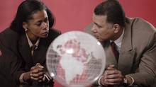 A businessman and businesswoman look at eaach other with a transparent globe in front of them. From photos.com (Getty Images/Comstock Images)