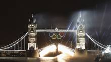 The Olympic rings are illuminated along with London's Tower Bridge as a speedboat driven by Britain's David Beckham and carrying the Olympic torch makes its way under the bridge to mark the opening ceremony of the London 2012 Olympic Games July 27, 2012. (Paul Hanna/REUTERS)