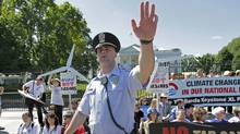 A U.S. Park Police officer motions journalists away from a group of environmental activists gathered outside the White House in Washington, Monday, Aug. 22, 2011. (AP/J. Scott Applewhite/AP/J. Scott Applewhite)