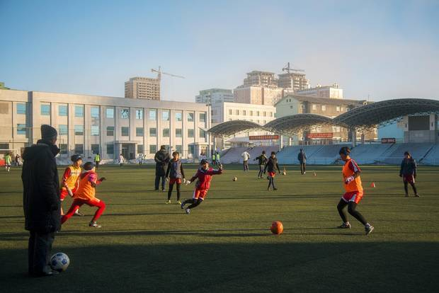 Children play an organized game of soccer after school. In this sports-mad society, pitches such as this one with artificial grass and bleachers aren't an uncommon sight.