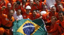 Brazilian President Luiz Inacio Lula da Silva, centre, in hard hat, poses with Petrobras workers. (JAMIL BITTAR)