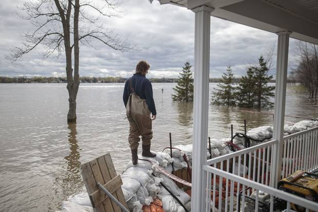 May 9: Patrice Pepin walks along a barrier of sandbags holding back the Ottawa River's waters at the home of his brother Christian Pepin and wife Marie-Pierre Chalifoux in Saint-Andre-d'Argenteuil, 90 kilometres west of Montreal.