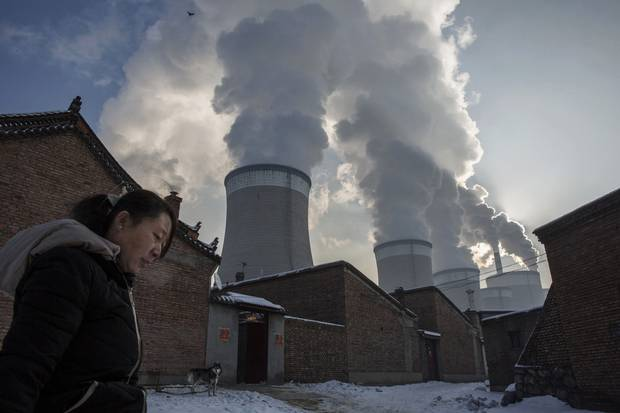 A woman walks out of her house next to a coal-fired power plant on Nov. 26, 2015, in Shanxi, China.
