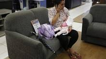 A woman sits on a couch with her baby as she talks on her mobile phone at a Casas Bahia store in Sao Paulo Feb. 7, 2013. After a spending spree in recent years, Brazilian consumers are acquiring more conservative habits. (NACHO DOCE/REUTERS)