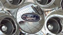 A Ford logo is displayed on a wheel at a car dealership in Omaha, Neb. (Nati Harnik/AP Photo)
