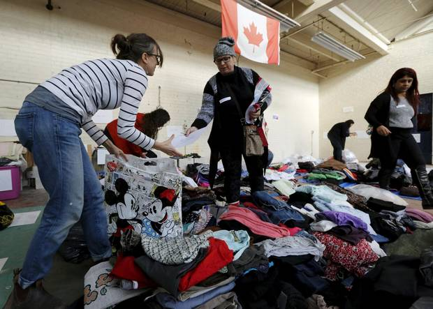 Clothing donated for an expected influx of Syrian refugees is sorted by volunteers for size and gender at a theatre rehearsal space in Toronto on Nov. 24, 2015.