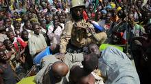 "A Malian soldier pushes suspected Islamist extremists to lay in the back of the army truck in Gao, northern Mali, Tuesday Jan. 29, 2013. Four suspects were arrested after being found by a youth militia calling themselves the ""Gao Patrolmen"". Malian soldiers prevented the mob from lynching them. (AP Photo/Jerome Delay"