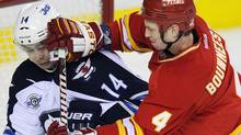 Calgary Flames' Jay Bouwmeester (R) pushes Winnipeg Jets' Tim Stapleton in front of the net during the second period of their NHL hockey game in Calgary, Alberta March 9, 2012. REUTERS/Todd Korol (Todd Korol/Reuters)
