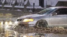 A motorist moves along a flooded street in Montreal, Monday, January 28, 2013, following a water main break. (Graham Hughes/THE CANADIAN PRESS)
