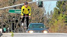 Google co-founder Sergey Brin rides outside its California headquarters. The company has added bicycle routes to Google Maps for 150 U.S. cities.