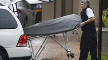 The second of six bodies is removed from the apartment tower where six men were found dead on Oct. 20, 2007, in a Surrey, B.C., high-rise. (Jeff Vinnick for The Globe and Mail)